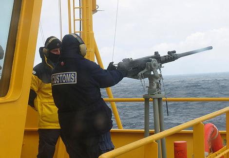 Customs officers fire a machine-gun on board Oceanic Viking